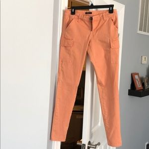 Peach colored ankle jeans.